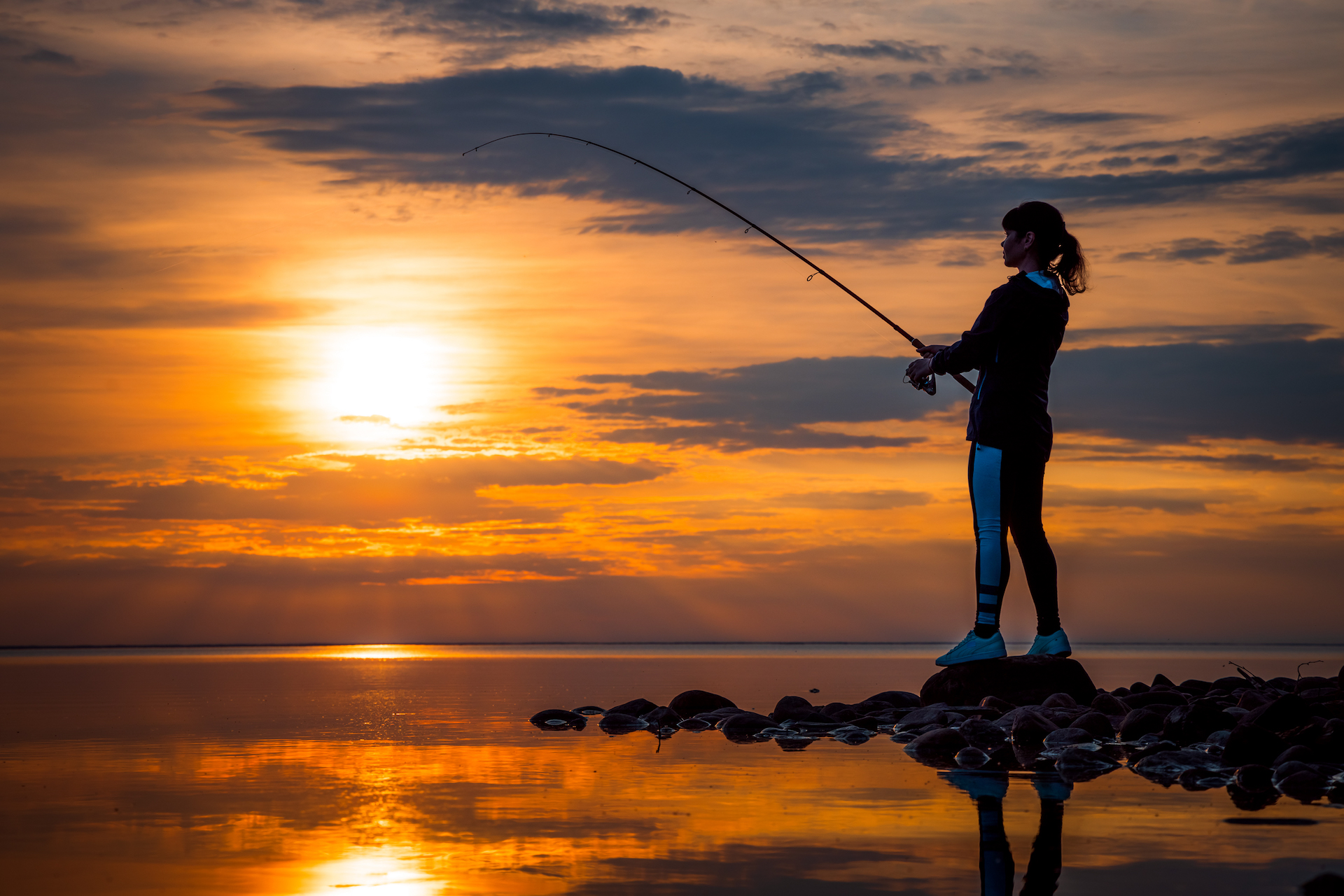 image of woman fishing at sunset from waterfront hotel